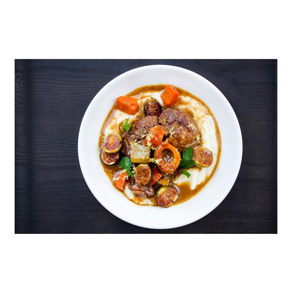 Rounds of cooked veal osso bucco, fig halves, carrot chunks & lemon zest on a bed of pureed white parsnip & brown gravy