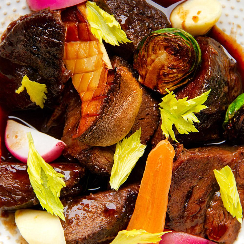 Braised beef cheeks with chanterelles and honeyed baby turnips in a white bowl