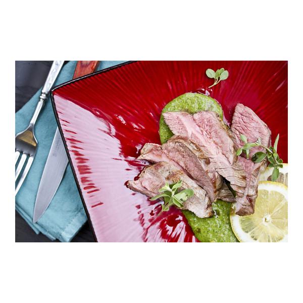 Roasted, sliced, boneless leg of lamb with herb & almond pesto & lemon on red plate, recipe