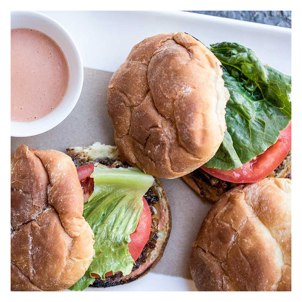 Grass-fed Angus beef hamburgers on buns with lettuce & tomato