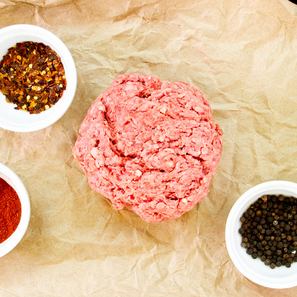 Raw ground grass-fed beef patty on butcher paper with ground & whole peppercorns