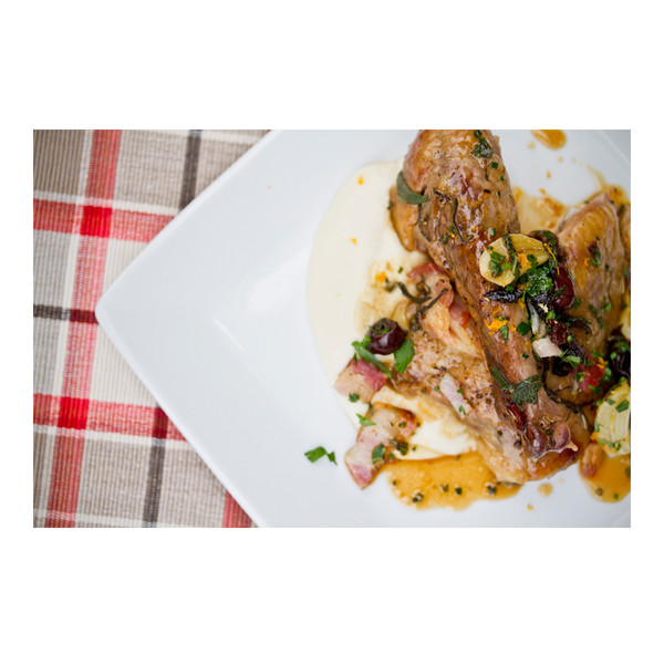 Plaid cloth, square white plate, cooked guinea fowl leg, sunchoke puree, brown sauce, chopped herbs, sliced garlic & prunes