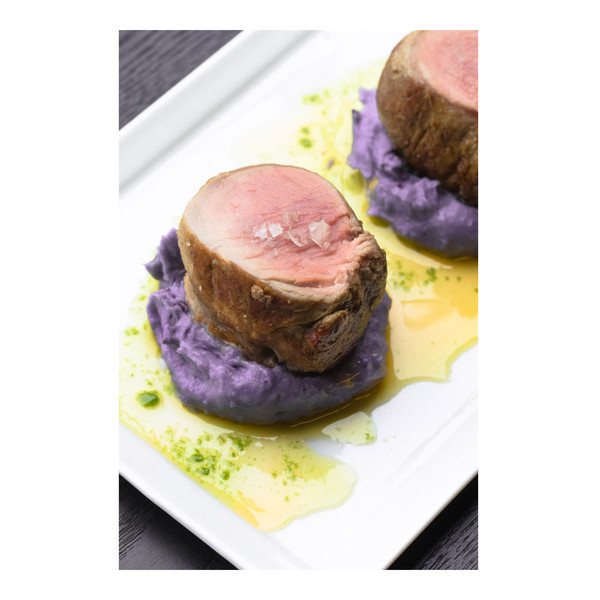 medallions of cooked Iberico pork tenderloin sprinkled with salt flakes on top of purple potato puree on a white plate in a pool of parsley oil