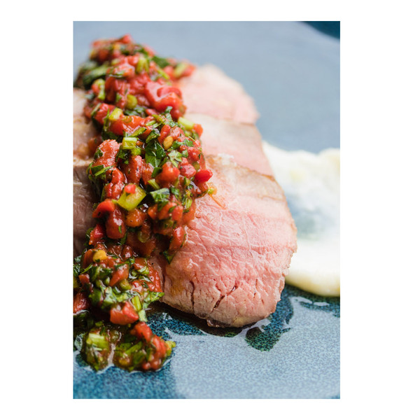 Spanish Iberico pork presa (shoulder eye steaks) with piquillo pepper & parsley on a plate with white sauce
