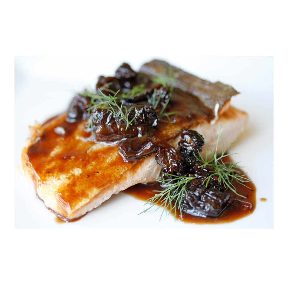 Cooked wild keta salmon fillet, skin side up, topped with a dark brown mushroom sauce & fresh herb sprigs