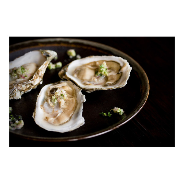 Round plate with 3 raw Shigoku oysters on the half shell sprinkled with grated wasabi & minced herbs