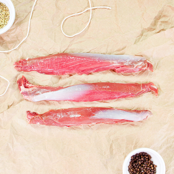 raw lamb tenderloins with a bowl of peppercorns & string on butcher paper