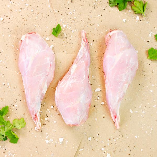 3 raw rabbit hind legs on brown butcher paper sprinkled salt, pepper & herb leaves