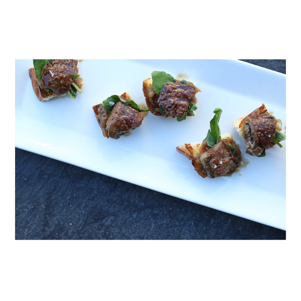 A white plate with 5 pieces of rabbit livers with honey/coffee-roasted shallot on brioche crostinis