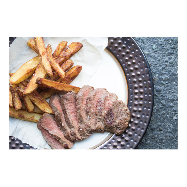 cooked, sliced flat iron steak next to fried potatoes on a white plate with a black rim