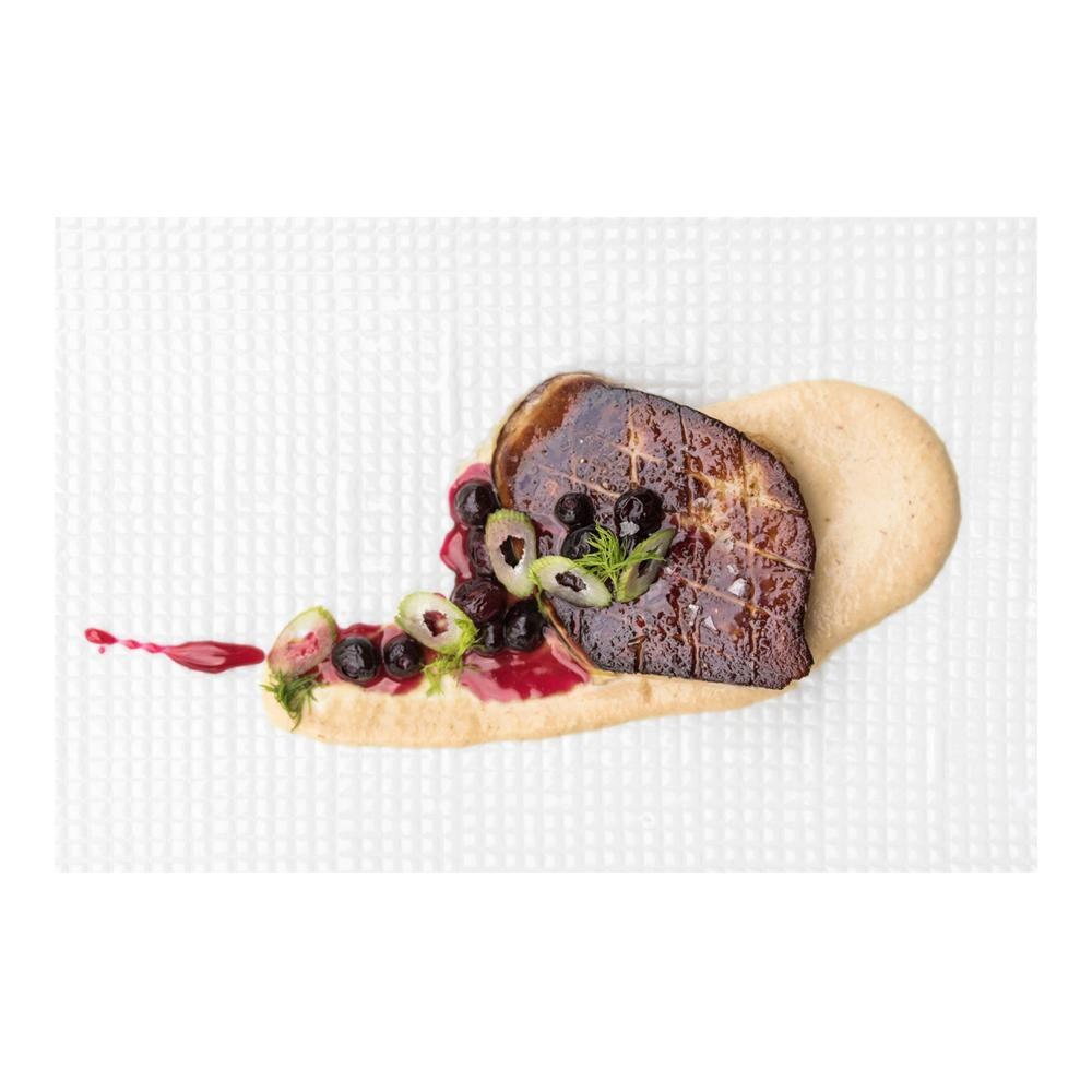 Beige sauce beneath a slice of seared grade B foie gras topped with blueberry sauce, whole blueberries & fennel slices