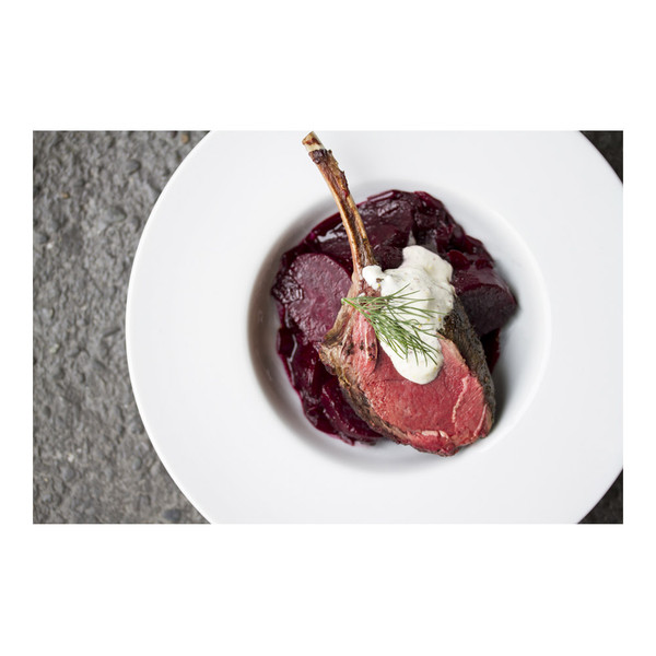 Sliced red beets in a white bowl with a cooked venison chop, a spoonful of horseradish cream and a sprig of fresh dill on top