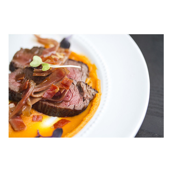 Sliced cooked venison denver leg meat on a white plate with orange sweet potato puree, diced prosciutto & a green herb sprig