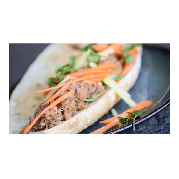 pineapple braised wild boar boneless leg meat sandwich with carrot & pineapple sticks and cilantro leaves on a torpedo roll