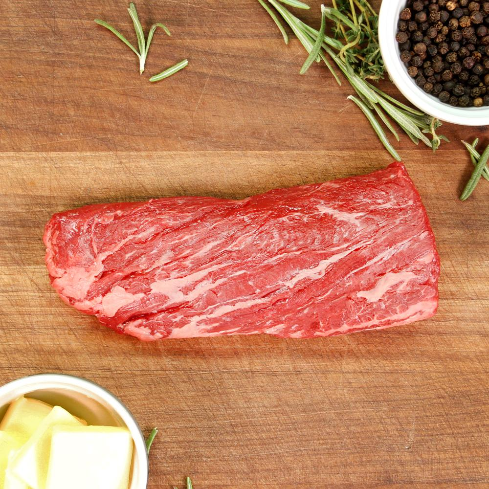 New Zealand grass-fed Angus beef hanger steak on a wooden board surrounded rosemary sprigs, a bowl of peppercorns & a bowl of butter