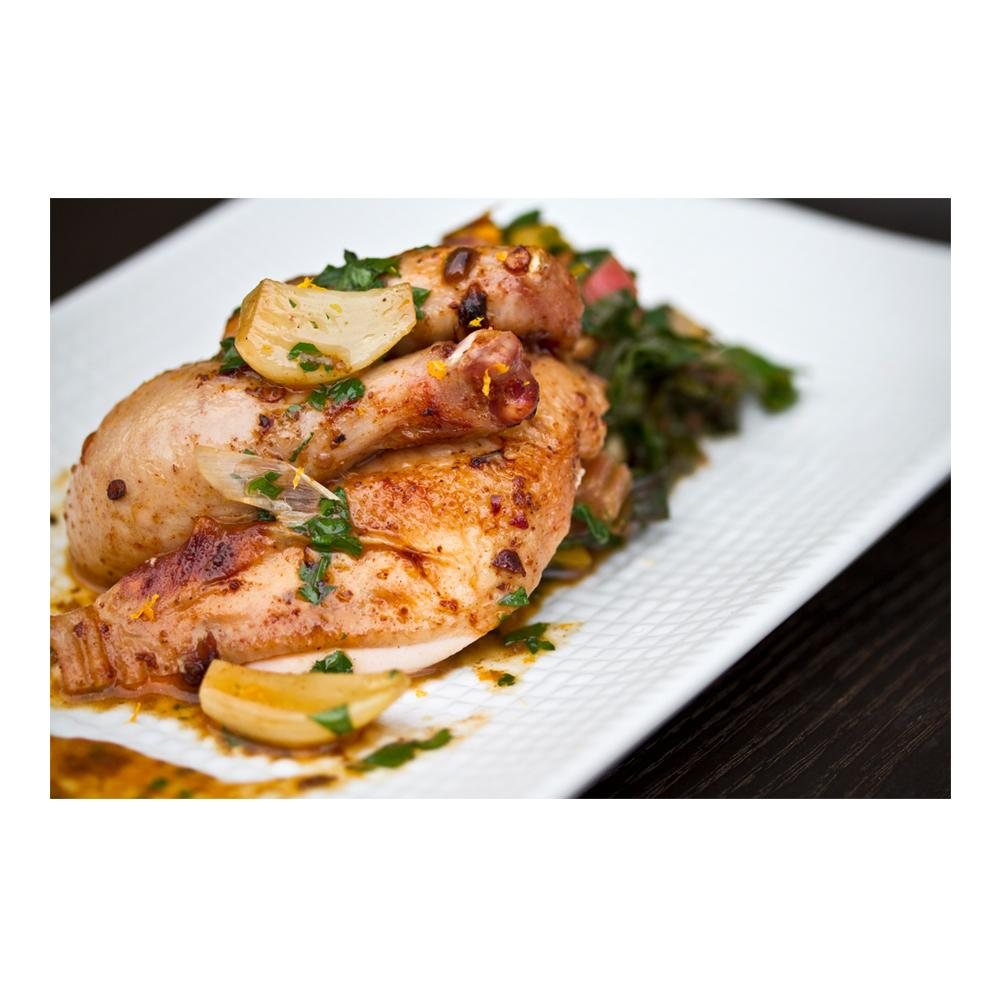 a white plate with cooked poussin (young chicken) pieces, garlic cloves & greens