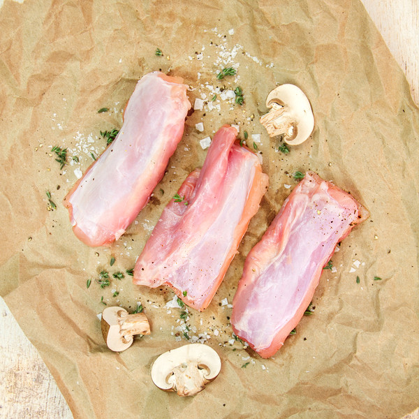 Raw boneless rabbit saddles on butcher paper with seasonings and mushrooms