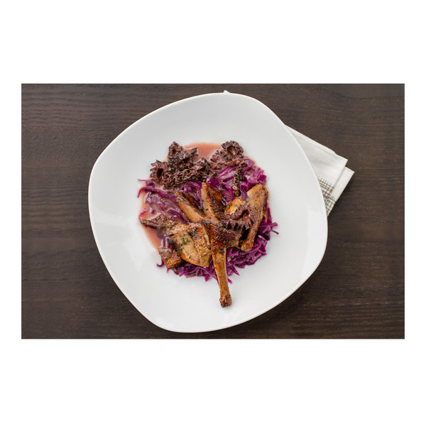 Split, seared squab with morels, red cabbage & pinot noir sauce on a white plate with napkin