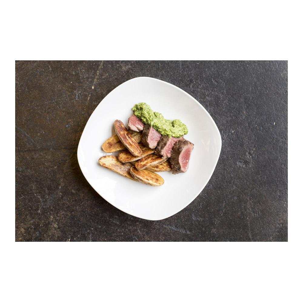 Green sauce & roasted fingerling potato halves flanking 4 slices of cooked venison tenderloin on a square white plate