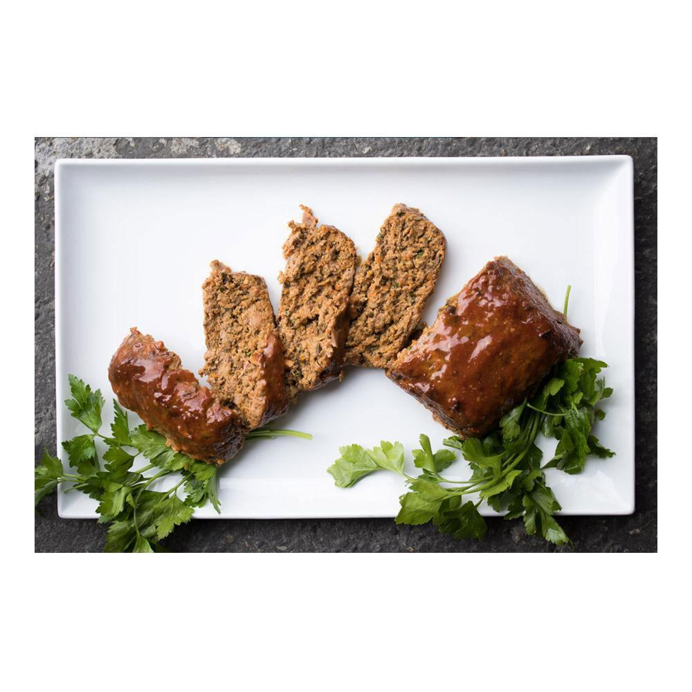 Glazed wild boar meatloaf slices & parsley sprigs fanned out on a rectangular white plate